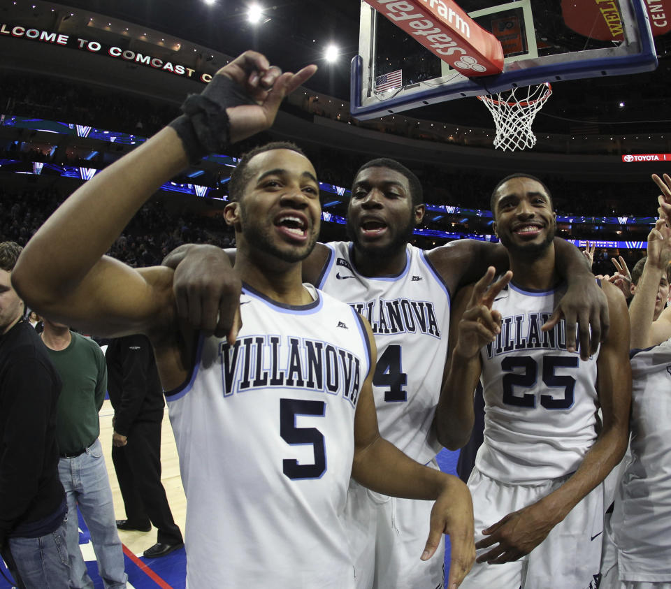 Villanova's Phil Booth, left, celebrates the win with Eric Paschall, center, and Mikal Bridges after the second half of an NCAA college basketball game against Georgetown, Saturday, March 3, 2018, in Philadelphia. Villanova won 97-73. (AP Photo/Chris Szagola)