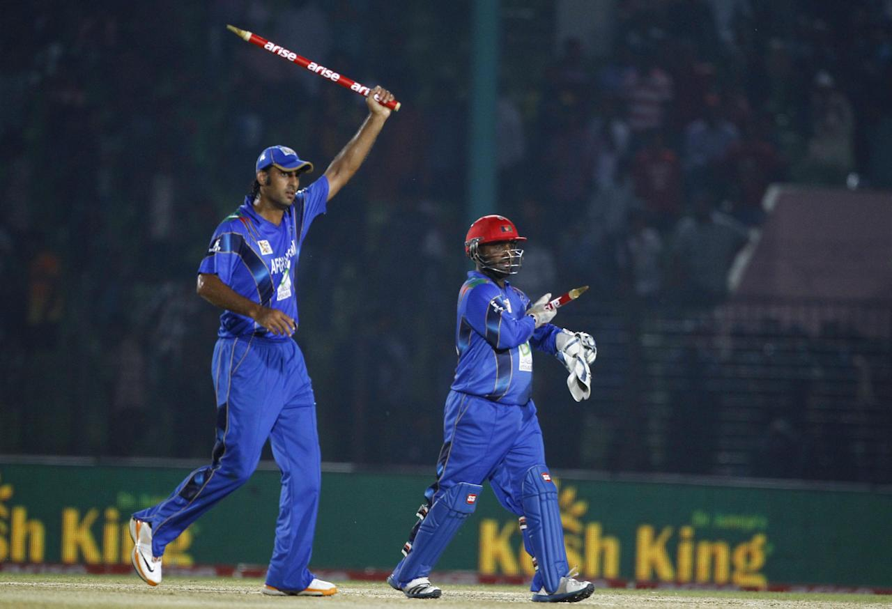 Afghanistan's wicketkeeper Mohammad Shahzad, right, and Shapoor Zadran celebrate after winning the Asia Cup one-day international cricket tournament against Bangladesh in Fatullah, near Dhaka, Bangladesh, Saturday, March 1, 2014. (AP Photo/A.M. Ahad)
