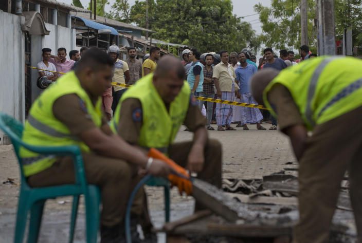 Police officers collect evidence from a site of a gun battle between troops and suspected Islamist militants as neighbors gather to watch in Kalmunai, Sri Lanka, Sunday, April 28, 2019. Police in Ampara showed The Associated Press on Sunday the explosives, chemicals and Islamic State flag they recovered from the site of one security force raid in the region as Sri Lanka's Catholics celebrated at televised Mass in the safety of their homes. (AP Photo/Gemunu Amarasinghe)