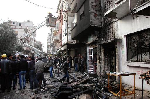 Syrians look at damage after an alleged mortar attack by opposition forces in Homs on January 9, 2014