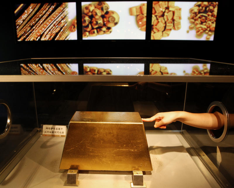 A visitor touches a 220 kg (485 lbs.) gold bar, worth around $12.8 million at today's price, on display at the Jinguashi Gold Ecological Park in Xinbei city September 16, 2011. The Jinguashi Gold Ecological Park said the gold bar is Taiwan's largest. REUTERS/Pichi Chuang (TAIWAN - Tags: BUSINESS SOCIETY TPX IMAGES OF THE DAY)