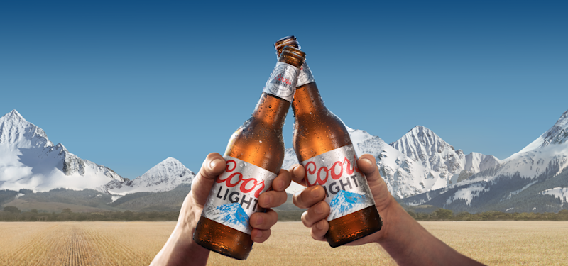 Two Coors Light bottles in front of mountains.