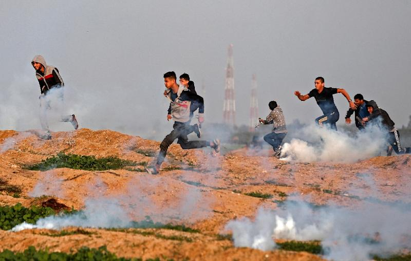 Palestinian protesters run away from tear gas fired by Israeli forces during clashes along the border with the Gaza strip
