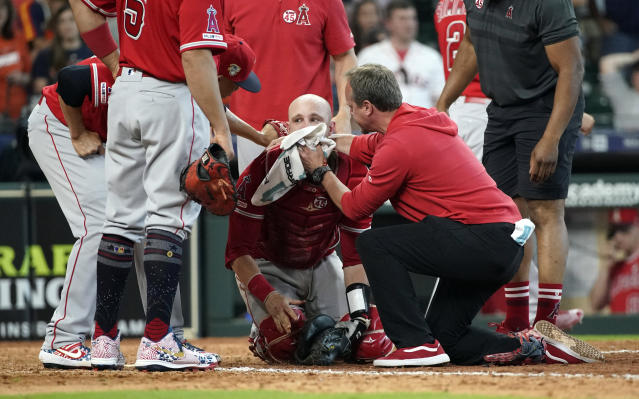 Los Angeles Angels' Jonathan Lucroy, center, is helped by medical personnel after colliding with Houston Astros' Jake Marisnick during the eighth inning of a baseball game Sunday, July 7, 2019, in Houston. (AP Photo/David J. Phillip)