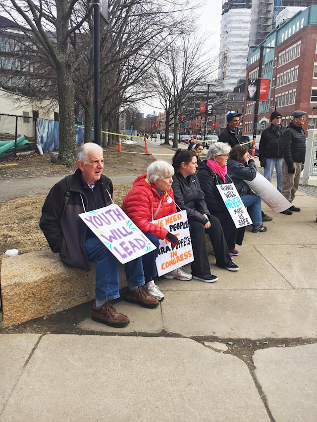 <p>Adults sit in support of protesters Boston. (Photo: Dave Cronin for Yahoo Lifestyle) </p>