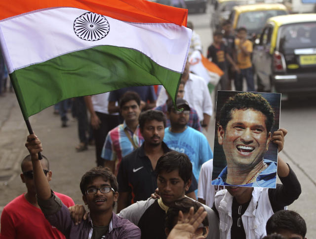 Supporters who line up to watch the last test match of Indian cricketer Sachin Tendulkar, hold his photo and wave an Indian flag in Mumbai, India, Thursday, Nov. 14, 2013. Tendulkar plays his world-record 200th and last test from Thursday in a hometown stadium for which tickets could have been sold 10 times over. (AP Photo/Rafiq Maqbool)