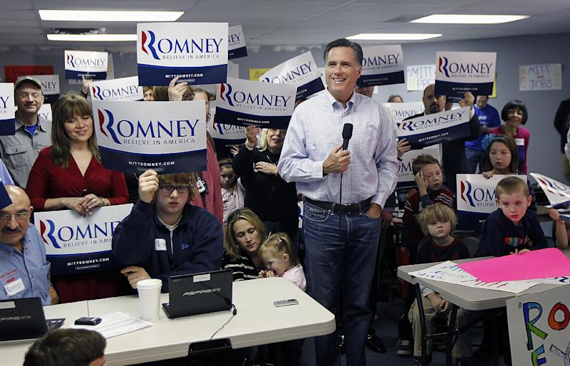 Volunteers hold up signs behind Republican presidential candidate, former Massachusetts Gov. Mitt Romney as he takes questions from reporters while visiting a campaign call center in Livonia, Mich., Tuesday, Feb. 28, 2012. (AP Photo/Gerald Herbert)