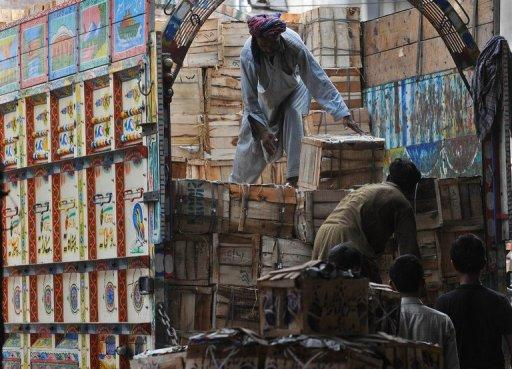 Pakistani men remove mango boxes from a truck at a vegetable market in Lahore in 2011