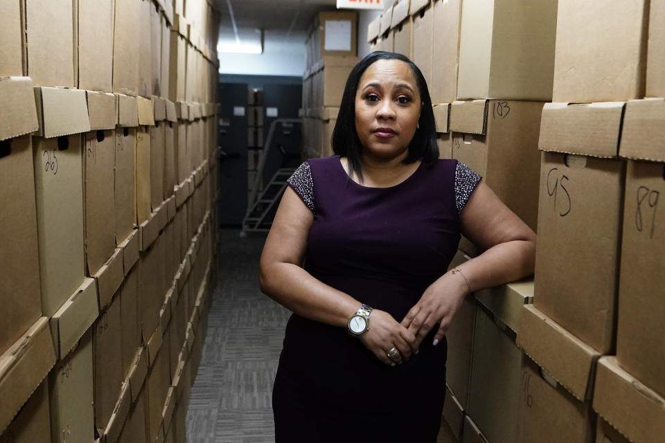 Fulton County District Attorney Fani Willis poses among boxes containing thousands of primal cases at her office, Wednesday, Feb. 24, 2021, in Atlanta. (AP Photo/John Bazemore)
