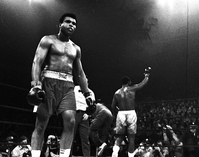 <p>A battered Muhammad Ali walks back to his corner as a triumphant Joe Frazier, background, celebrates his title defense after the 15th round of their title bout at New York's Madison Square Garden on March 8, 1971. (AP Photo) </p>