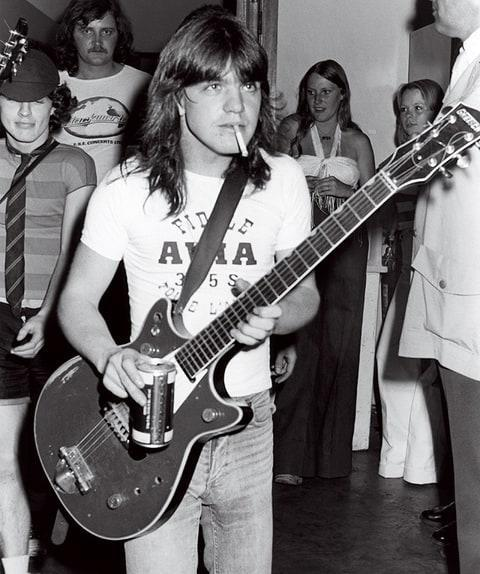 """<span class=""""caption"""">1976 - Photo of AC/DC and Malcolm YOUNG and Angus YOUNG; Malcolm Young and Angus Young (behind) backstage </span> <span class=""""credit"""">Bob King/Getty</span>"""