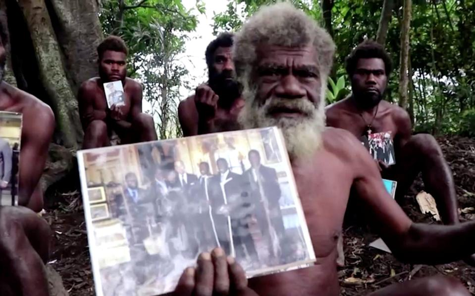 Chief Yapa from the village of Ikunala offered condolences to the British royal family, holding a photo of himself and other local men who went to the UK in 2007 to meet Prince Philip - Reuters