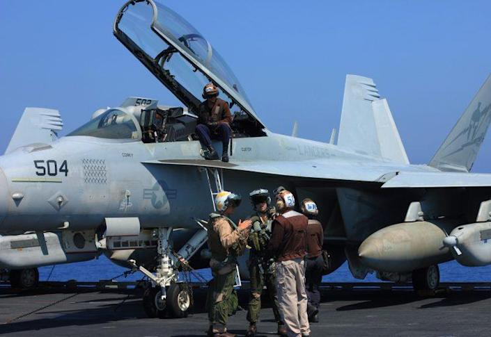 Fighter pilots and aircraft controllers prepare for daily takeoffs.