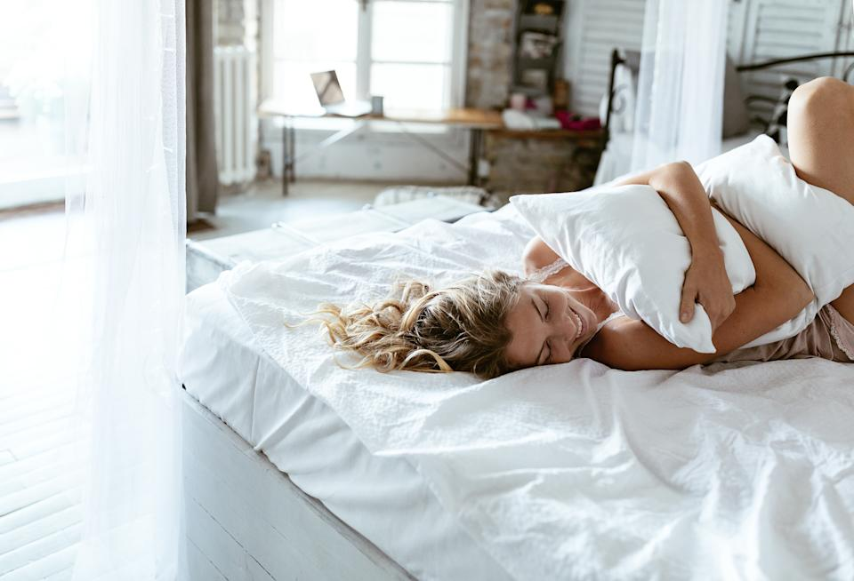 Woman lying in bed hugging a pillow