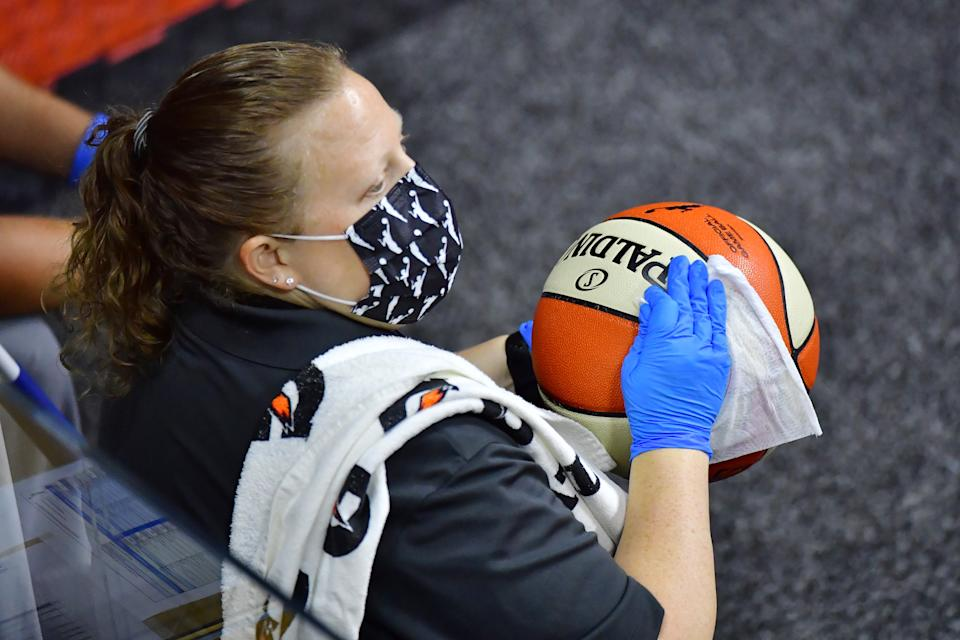 A staff member sanitizes a game ball that went out of bounds as part of the league's COVID-19 protocols. (Photo by Julio Aguilar/Getty Images)