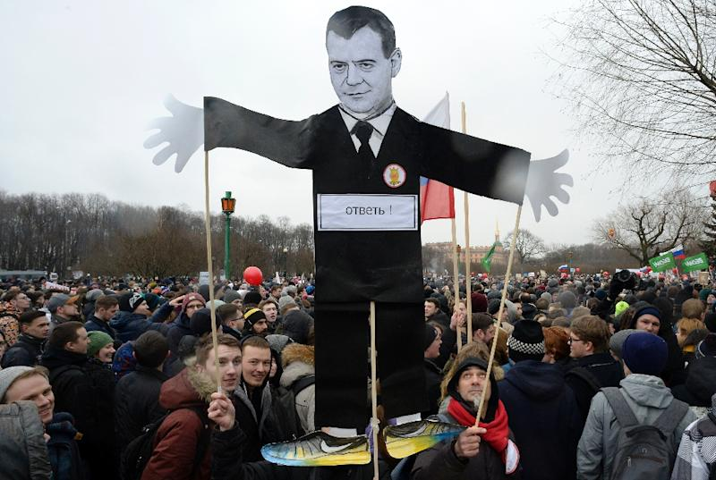 Opposition supporters with a cutout figure depicting Prime Minister Dmitry Medvedev participate in an anti-corruption rally in central Saint Petersburg on March 26, 2017 (AFP Photo/Olga MALTSEVA)
