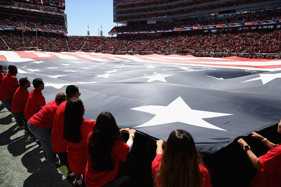 Volunteers hold up a giant flag at a Lions-49ers game in Santa Clara, Calif.  (Ezra Shaw/Getty Images)