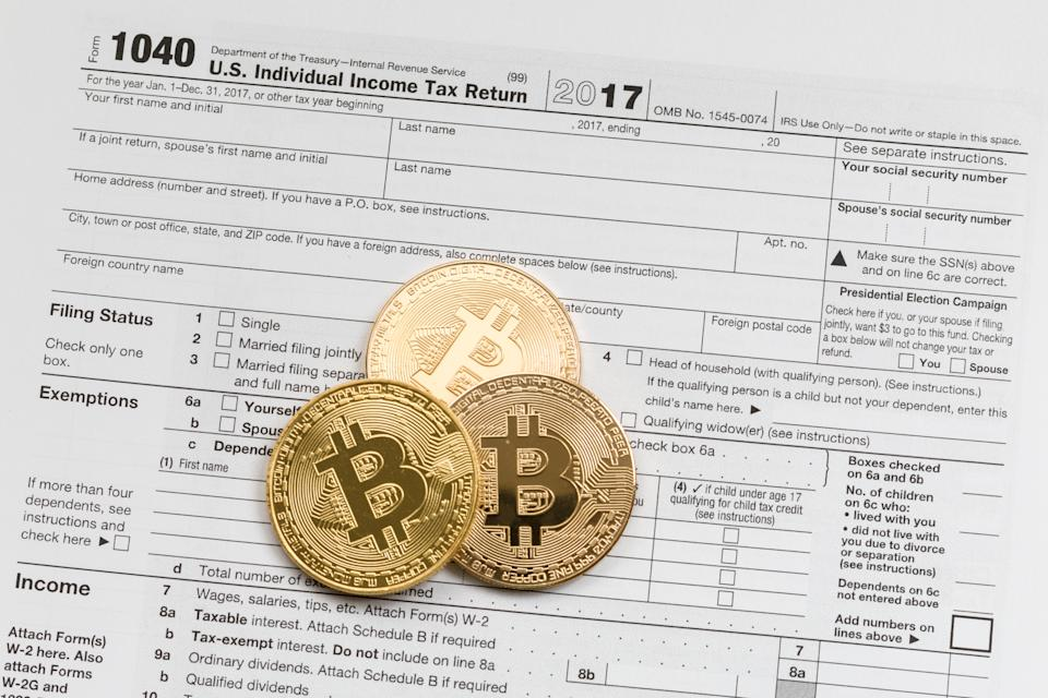 Three bitcoins on the U.S. Individual Income Tax Return.  Bitcoin is cryptocurrency and worldwide payment system. Bitcoin is the first decentralized digital currency, as the system works without a central bank or single administrator.