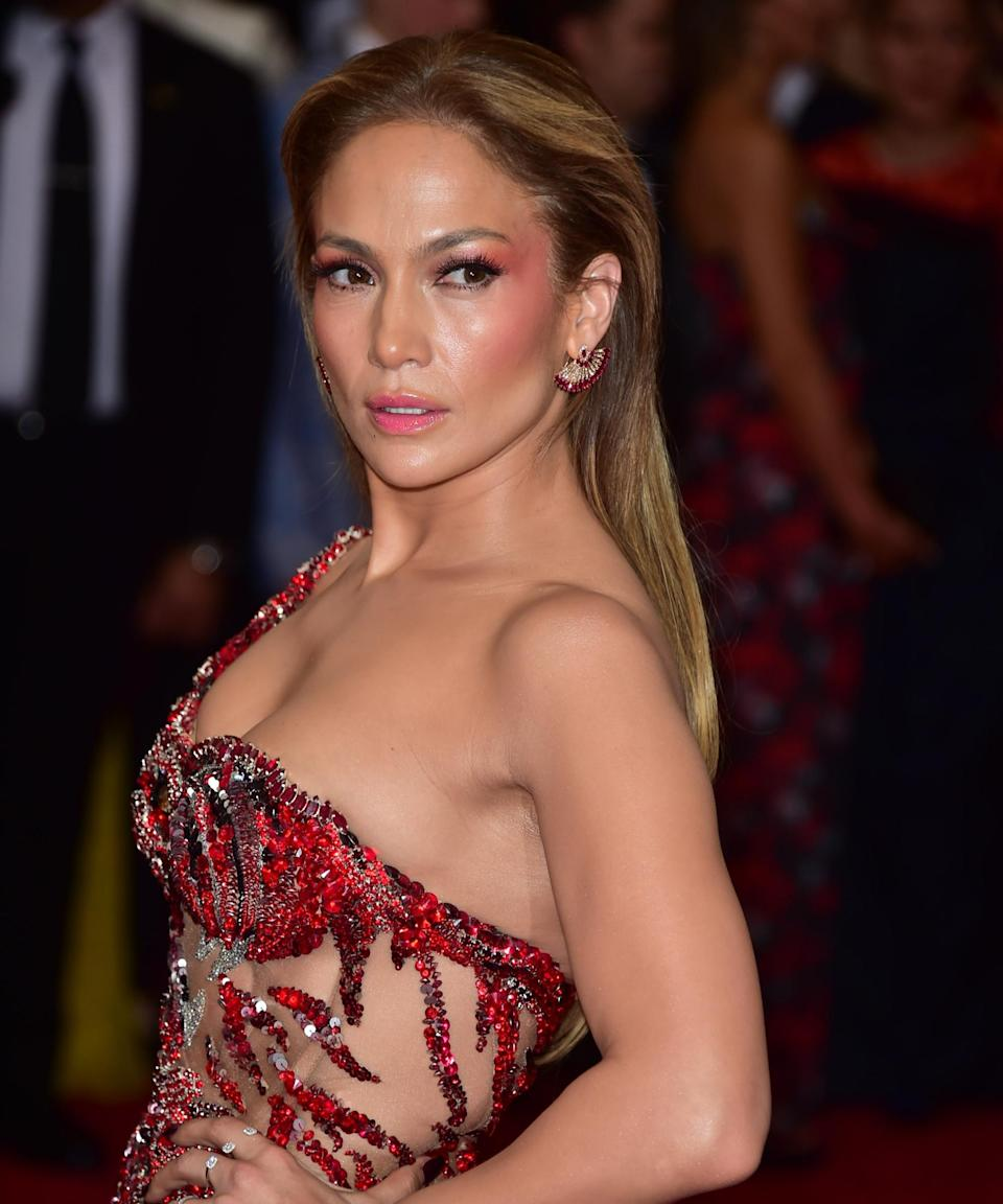 """<h3>2014</h3><br>Lopez's poppy-colored lipstick and dramatic coordinating cheekbones at the 2014 Met Gala is a makeup look for the books.<span class=""""copyright"""">Photo: George Pimentel/WireImage.</span>"""