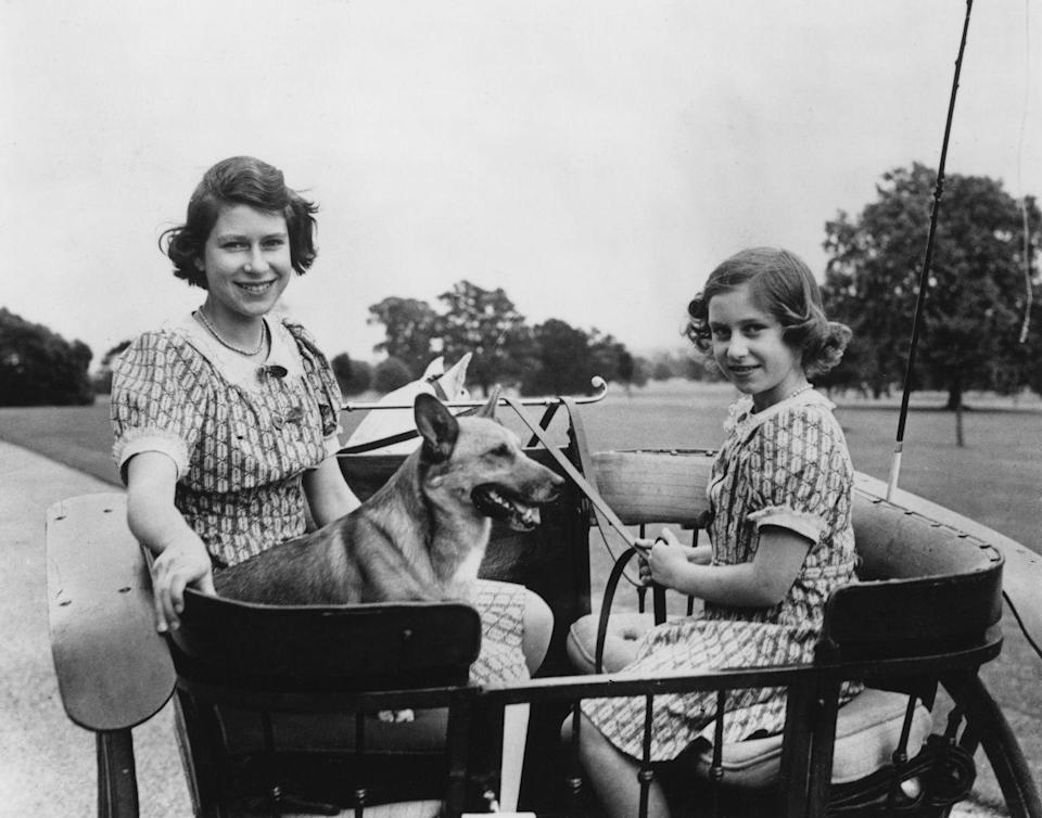 <p>Princess Elizabeth and Princess Anne play with one of the family's corgis.</p>