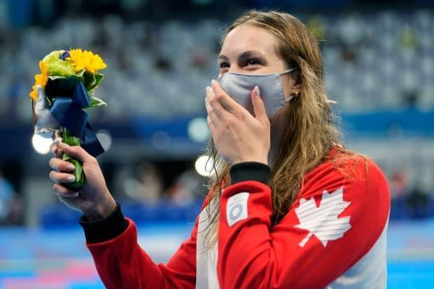 Penny Oleksiak of Canada waves her flowers after winning the bronze medal in the women's 200-metre freestyle final at the Tokyo Olympic Games. (Martin Meissner/The Associated Press - image credit)