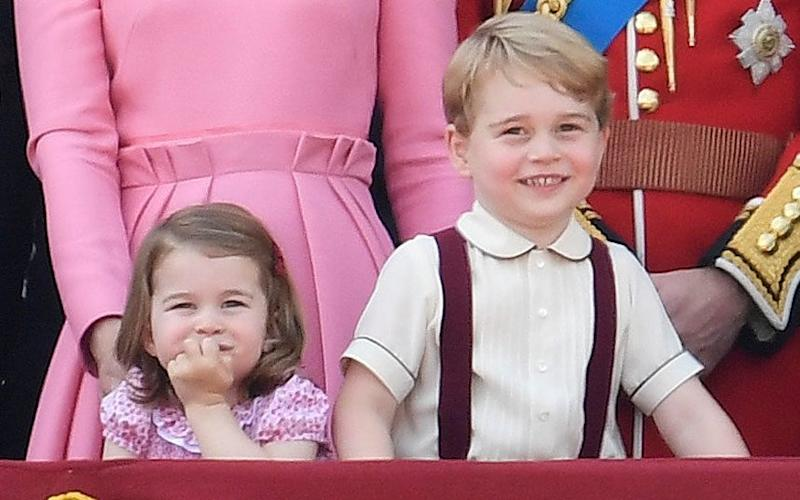 Prince George and Princess Charlotte watch air show from the balcony of Buckingham Palace - Credit: Reuters