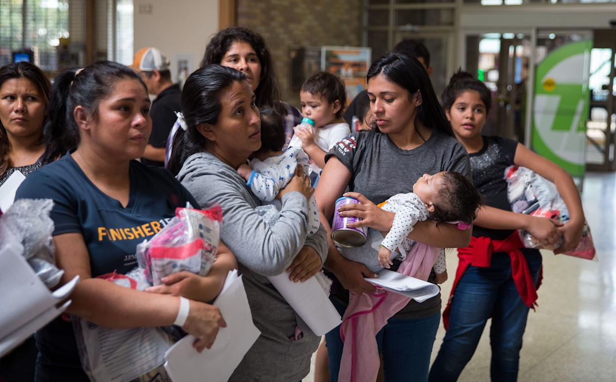 "Immigrants wait to head to a nearby Catholic Charities relief center after being dropped off at a bus station shortly after release from detention through ""catch and release"" immigration policy on June 17 in McAllen, Texas. (Photo: Loren Elliott/Getty Images)"