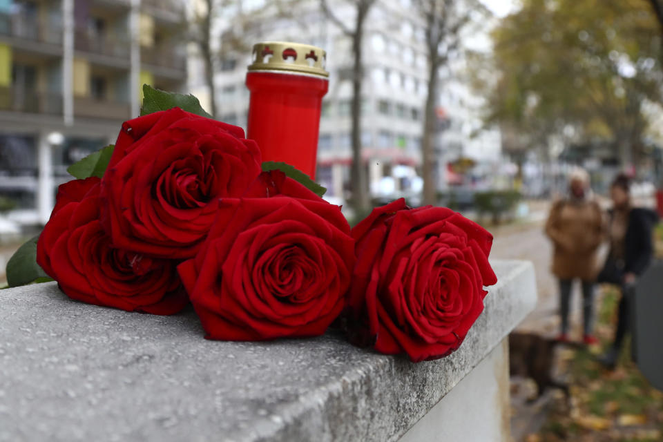 Roses lay besides a candle in Vienna, Austria, Tuesday, Nov. 3, 2020. Police in the Austrian capital said several shots were fired shortly after 8 p.m. local time on Monday, Nov. 2, in a lively street in the city center of Vienna. Austria's top security official said authorities believe there were several gunmen involved and that a police operation was still ongoing. (AP Photo/Matthias Schrader)
