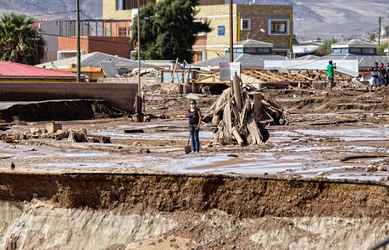 A woman stands in a street that was flooded in Chanaral, after heavy rainfall caused the Copiapo river to overflow, and flooding in parts of the city in nothern Chile, April 1, 2015 (AFP Photo/Patricio Miranda)