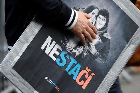 """FILE PHOTO: A man attends a protest rally in reaction to the murder of Slovak investigative reporter Jan Kuciak and his fiancee Martina Kusnirova, in Bratislava, Slovakia April 5, 2018. The placard shows portraits of Jan Kuciak and Martina Kusnirova and reads """"Not enough"""". REUTERS/Radovan Stoklasa"""