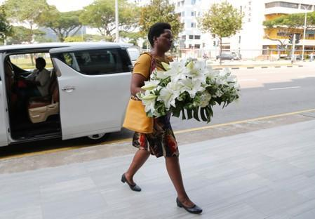 A visitor arrives with a wreath at funeral parlour Singapore Casket, where the body of late former Zimbabwe's President Robert Mugabe is being held in Singapore