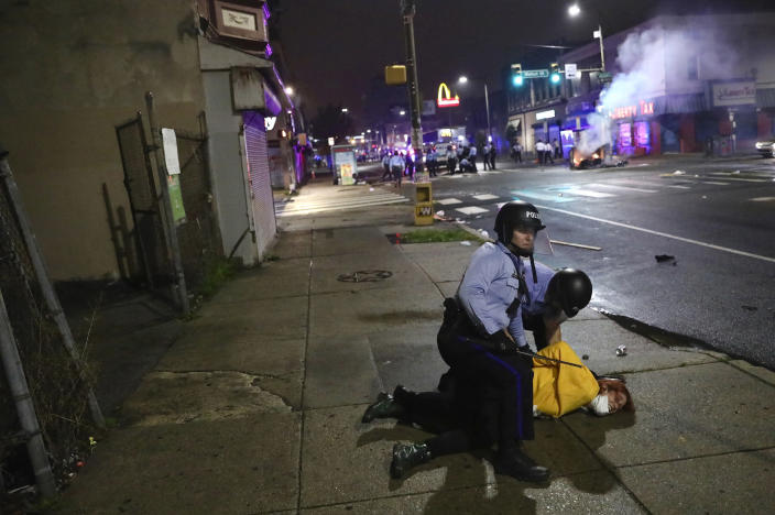 Image: Police handcuff a protester after charging at a crowd in West Philadelphia early Tuesday. (Tim Tai / AP)