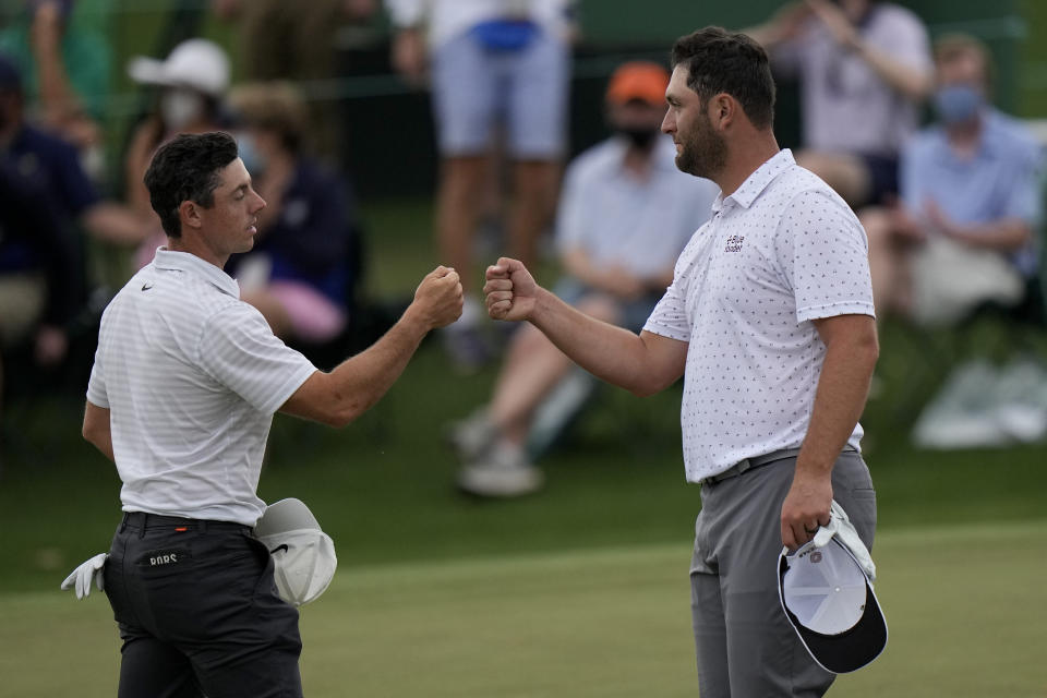 Rory McIlroy, of Northern Ireland, bumps fists with Jon Rahm, of Spain, on the 18th green during the second round of the Masters golf tournament on Friday, April 9, 2021, in Augusta, Ga. (AP Photo/Matt Slocum)