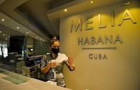 A receptionist sanitizes her hands at the Melia Habana Hotel in Havana -- Cuba is reopening its doors to foreign tourists after months of coronavirus-related closures, but will travelers return?