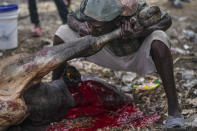 A butcher blows into the skin of a cow's leg in order to peel it off, on the first market day since the earthquake in Camp Perrin, Haiti, Friday, Aug. 20, 2021, six days after a 7.2 magnitude quake. (AP Photo/Fernando Llano)