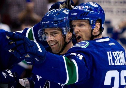 Vancouver Canucks' Dan Hamhuis, left, and Henrik Sedin, of Sweden, celebrate Hamhuis' goal against the Los Angeles Kings during the first period of an NHL hockey game in Vancouver, British Columbia, Saturday, March 2, 2013. (AP Photo/The Canadian Press, Darryl Dyck)