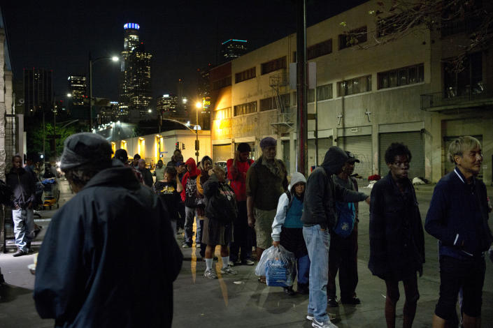 """FILE - In this Sept. 19, 2017, file photo, people line up for free food being given out in an area of downtown Los Angeles known as Skid Row. A fed up federal judge says a rain storm during the last week of January 2021 created """"extraordinarily harsh"""" conditions for homeless residents of Los Angeles and he has ordered city officials to meet with him at a Skid Row shelter to discuss how to address the worsening crisis of people living on the streets. (AP Photo/Jae C. Hong,File)"""