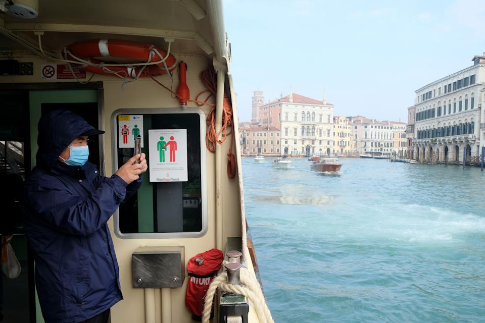 A tourist wearing a protective mask is seen inside a water bus, after two coronavirus cases have been confirmed in Italy, in Venice, Italy, January 31, 2020. REUTERS/Manuel Silvestri