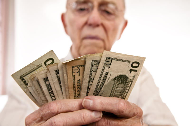 An elderly man counting a fanned pile of cash bills in his hands.