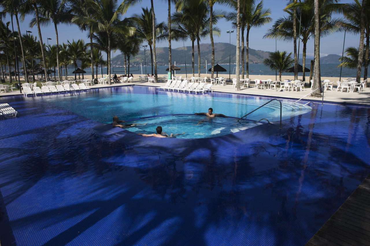 <p> FILE - In this May 8, 2014 file photo, guests wade in the pool at Hotel Portobello where Italy's soccer team will train and reside during the World Cup in Mangaratiba, Brazil. A Brazilian consumer defense agency said Monday, May 26, 2014 it's found past-expiration food at Hotel Portobello as well as the Royal Tulip Hotel where England's team will stay during the World Cup. The Rio de Janeiro state agency said that the inspections were part of an effort to enforce food safety codes ahead of next month's tournament. (AP Photo/Hassan Ammar, File) </p>