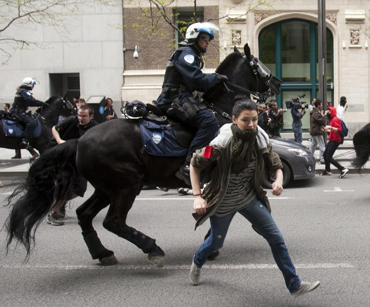 Police on horseback charge into a crowd of students protesting against tuition hikes in Montreal, Tuesday, May 15, 2012. A recent court injunction ordered the reopening of College Lionel-Groulx near Montreal. After several days of student pickets, which included some parents and teachers who wanted to support the declared strikers, riot police used chemical irritants to clear a path into the school today. Some students, along with faculty, eventually entered. Hours later, after staff meetings, the college issued a statement: Lionel-Groulx will remain closed for two more days(AP Photo/The Canadian Press, Ryan Remiorz)