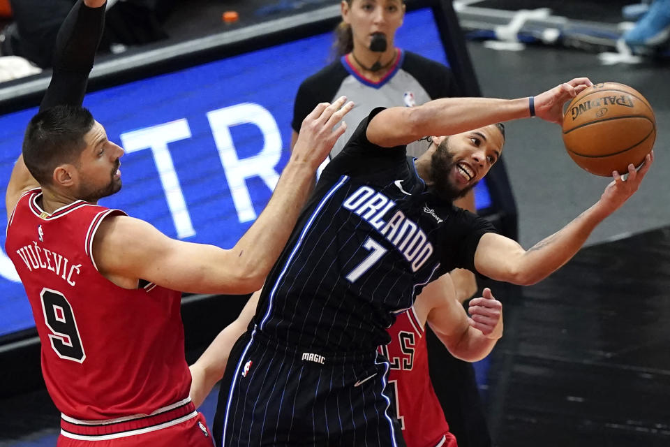 Orlando Magic guard Michael Carter-Williams (7) grabs a rebound next to Chicago Bulls center Nikola Vucevic, left, and guard Tomas Satoransky during the second half of an NBA basketball game in Chicago, Wednesday, April 14, 2021. (AP Photo/Nam Y. Huh)