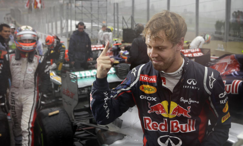 Red Bull driver Sebastian Vettel of Germany celebrates after the Formula One Brazilian Grand Prix at the Interlagos race track in Sao Paulo, Brazil, Sunday, Nov. 25, 2012.  Vettel overcame a first-lap crash to clinch his third straight Formula One championship title on Sunday, finishing sixth in an incident-filled Brazilian Grand Prix won by Jenson Button under pouring rain.(AP Photo/Ricardo Mazalan)