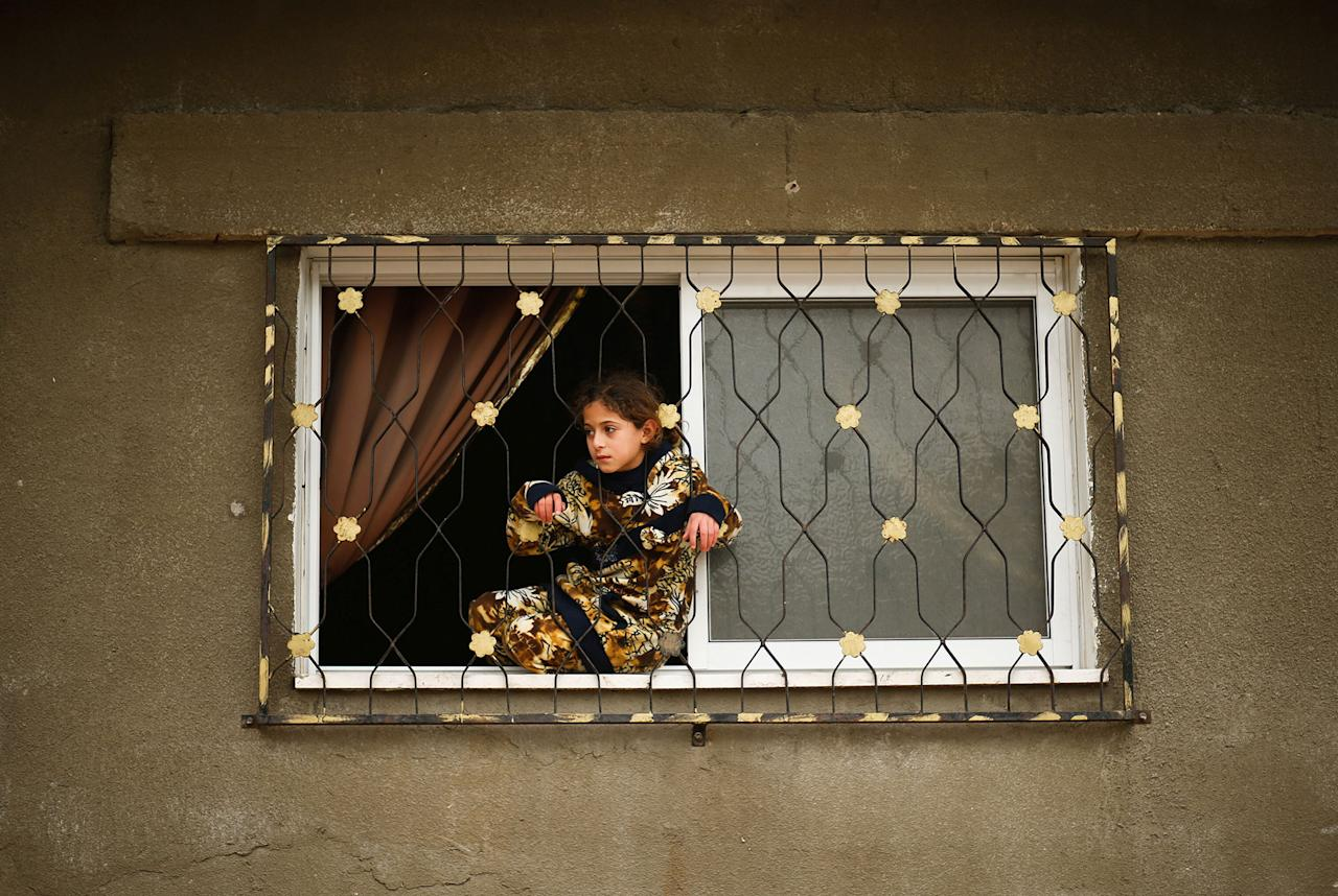 <p>A Palestinian girl looks out her family house following heavy rain in a neighbourhood in the northern Gaza Strip February 16, 2017. (Mohammed Salem/Reuters) </p>