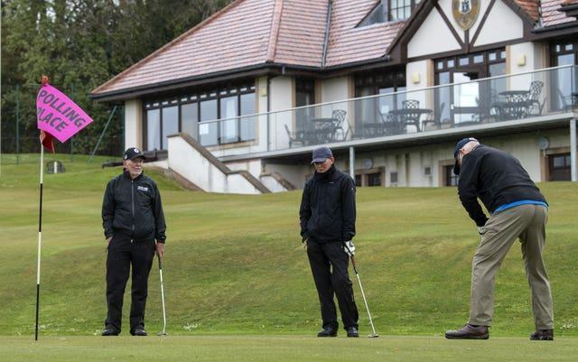 Golfers Colin Tait, Richard Wilson and Stewart Crawford practise putting as they arrive to cast their votes in the Scottish Parliamentary election at the polling station in the club house at the Merchants of Edinburgh Golf Club