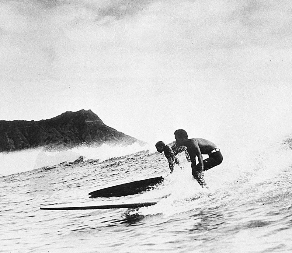 FILE - In this Jan. 9, 1935, file photo, two surfers ride the crest of a wave back to the beach in Honolulu, Hawaii. For some Native Hawaiians, surfing's Olympic debut is both a celebration of a cultural touchstone invented by their ancestors, and an extension of the racial indignities seared into the history of the game and their homeland. The Summer Games in Tokyo, which kick off this month, serve as a proxy for that unresolved tension and resentment, according to the Native Hawaiians who lament that surfing and their identity have been culturally appropriated by white outsiders who now stand to benefit the most from the $10 billion industry. (AP Photo/File)