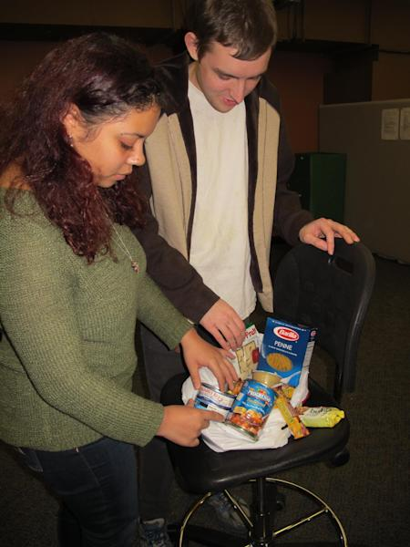 In this photo taken on Tuesday, March 4, 2014, at Stony Brook University, students Ruby Escalera-Nater, left, and Will Addison fill a bag of food to give to guests at the college's recently opened food pantry. Officials say there are a growing number of food pantries opening on college campuses across the country to assist students contending with rising education costs.(AP Photo/Frank Eltman)