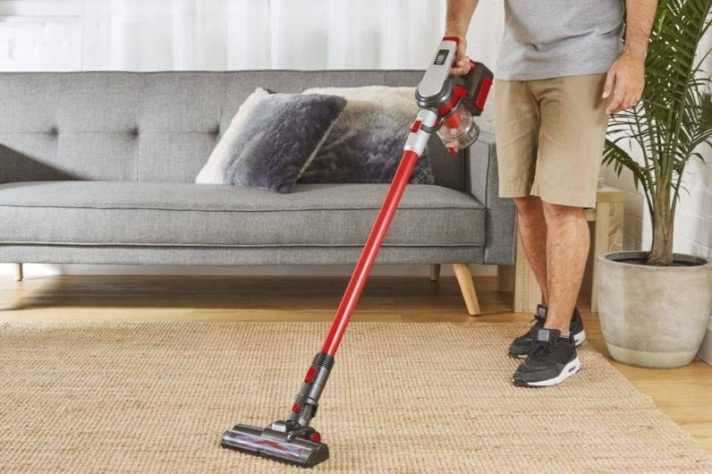 catalogue image shows man cut off from torso vacuuming with Aldi special buy vacuum