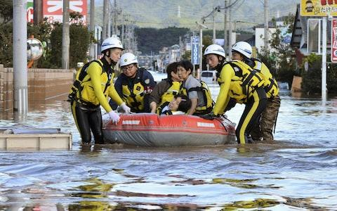Local residents sit in a boat as they are rescued from a flooded residential area following Typhoon Hagibis in Iwaki, Fukushima - Credit: JAPAN OUT/Reuters