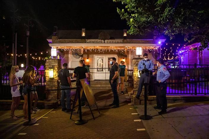Two Raleigh police officers stand outside the Cornerstone Tavern on Glenwood Avenue, which opened its doors for business despite Gov. Roy CooperÕs veto of legislation to reopen bars and a judgeÕs decision hours earlier denying a lawsuit brought against the governorÕs executive orders by the N.C. Bar and Tavern Association, on Friday, Jun. 26, 2020, in Raleigh, N.C.